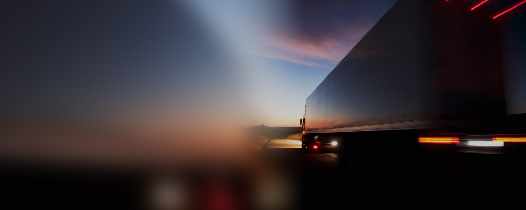 Truck on highway in motion with sunset sky